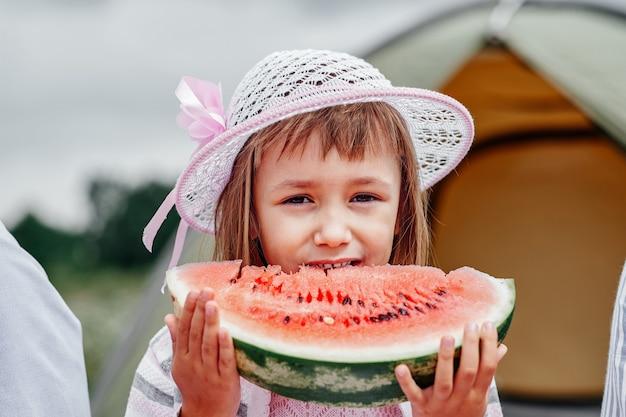 Portret małego chłopca na pikniku. dziecko jedzenie arbuza na łące.