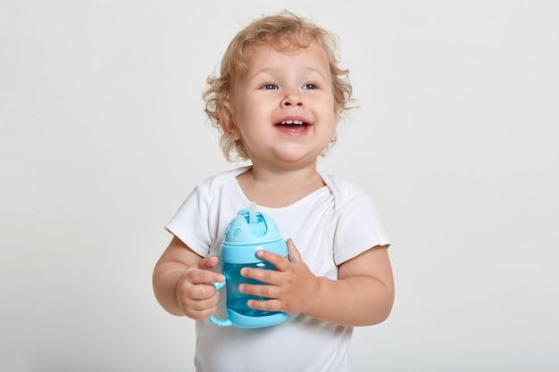 Portret małego chłopca o blond włosach, ubranego w białą koszulę, pozującego odizolowanego na jasnej ścianie z niebieską butelką na jedzenie dla niemowląt, chce wody pitnej, odwracając wzrok z podekscytowaną miną.