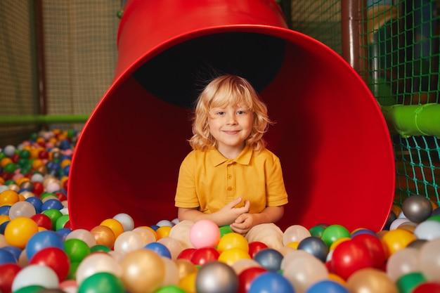 Portret małego chłopca patrząc na przód podczas zabawy w parku rozrywki
