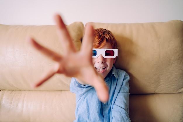 Portret małego chłopca próbującego sięgnąć i podnieść coś z szeroko otwartą ręką i palcami.