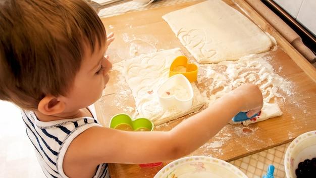 Portret małego chłopca robiącego ciasto na drewnianym blacie kuchennym