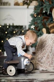 Portret małego chłopca siedzącego na vintage samolot zabawka w pobliżu choinki