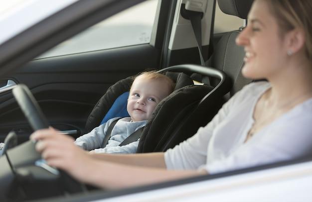 Portret małego chłopca siedzącego w samochodzie przy foteliku samochodowym