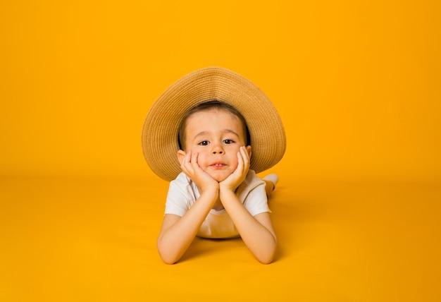 Portret małego chłopca w białej koszulce i słomkowym kapeluszu patrząc w kamerę na żółtej powierzchni z miejscem na tekst