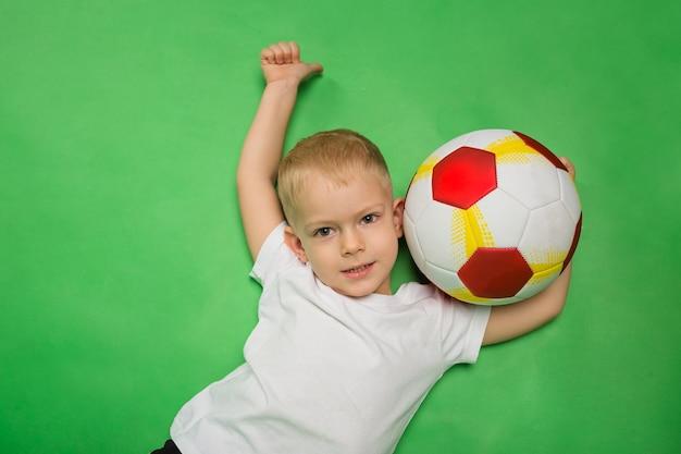 Portret małego chłopca w białej koszulce z piłką nożną na zielono