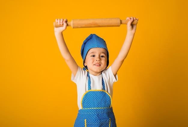 Portret małego chłopca w kapeluszu szefa kuchni i fartuchu, trzymając wałek do ciasta na żółtej powierzchni z miejscem na tekst