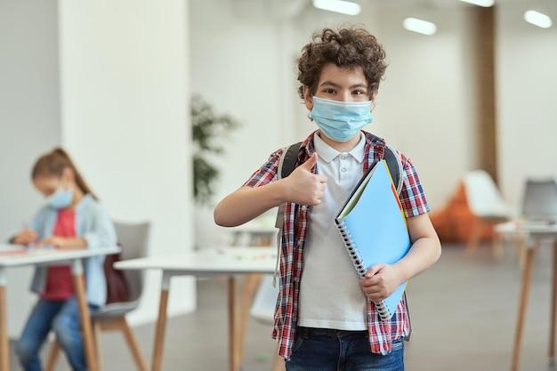 Portret małego chłopca w szkole noszącego maskę, aby zapobiec rozprzestrzenianiu się covid, patrząc na pokazującą kamerę