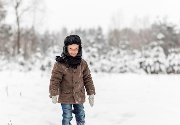 Portret małego chłopca w zimowym lesie