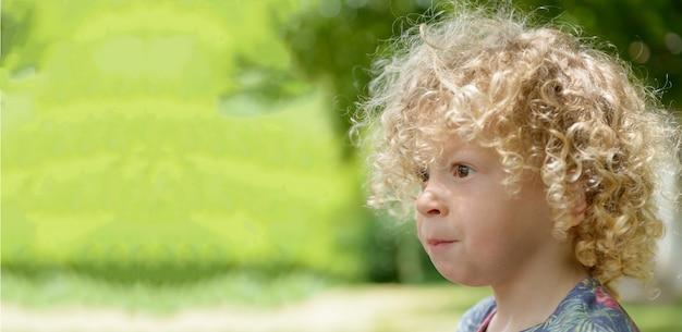 Portret małego chłopca z blond kręconymi włosami