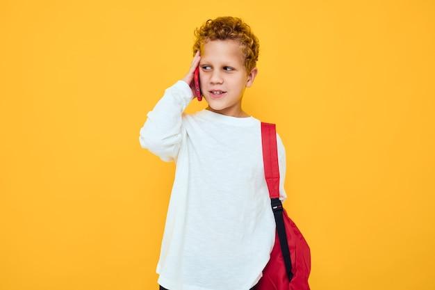 Portret małego chłopca z czerwonym plecakiem dzwoni na telefon na białym tle