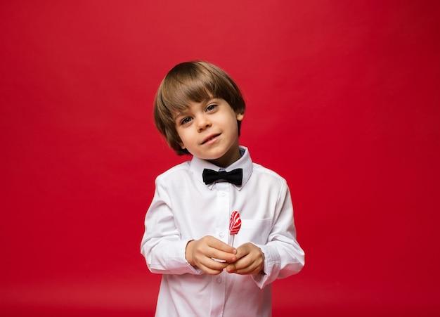 Portret małego chłopca z lizakiem na czerwono