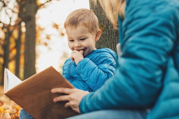 Portret małego cute dzieciak myśli podczas czytania książki na świeżym powietrzu z matką.