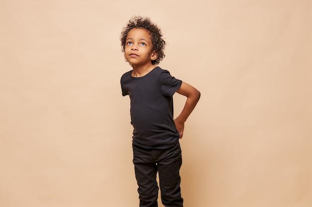 Portret małego czarnego chłopca afro american na białym tle