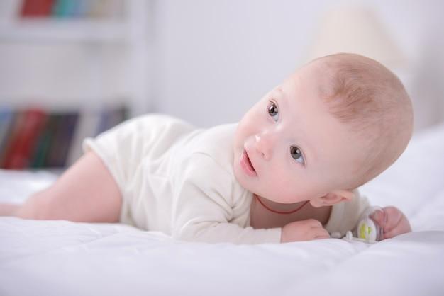 Portret małego dziecka bawiące się na łóżku.