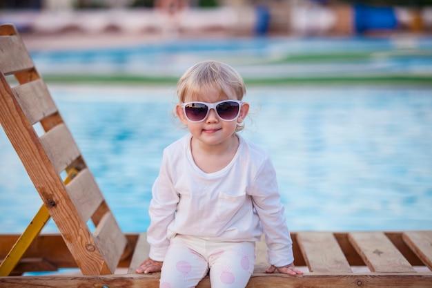 Portret małego dziecka na leżaku z osłonami przeciwsłonecznymi. szczęście, wakacje, kurort, podróż, uśmiech, lato, upał