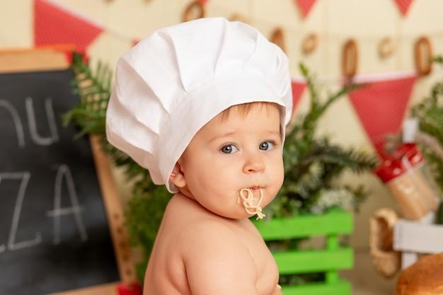 Portret małego dziecka w kapeluszu szefa kuchni ze spaghetti w ustach