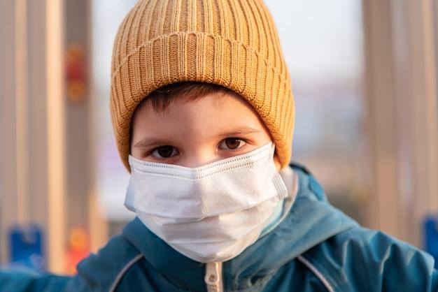 Portret małego dziecka w masce medycznej na ulicy podczas koronawirusa i pandemii covida - 19