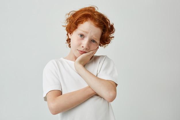 Portret małego ładnego chłopca z imbirowymi włosami i piegami, trzymając głowę znudzonymi rękami