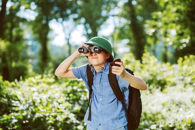 Portret małego odkrywcy z lornetką w lesie.