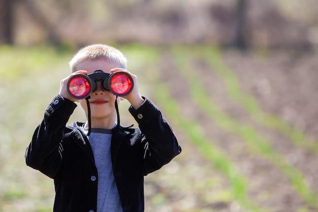 Portret małego ślicznego przystojnego ślicznego blond chłopiec ogląda uważnie coś przez lornetki w odległości