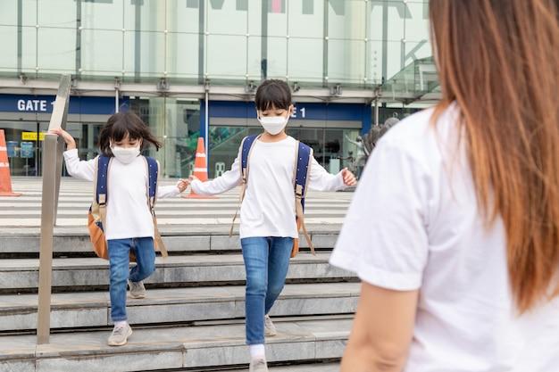 Portret małego słodkiego rodzeństwa azjatyckich dzieci noszących maskę na twarz i biorących torbę szkolną