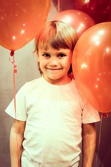 Portret małego szczęśliwego szczerego uśmiechniętego kaukaskiego pięcioletniego chłopca w białej koszulce z czerwonymi balonami na tle szarej ściany podczas obchodów jego urodzin w domu