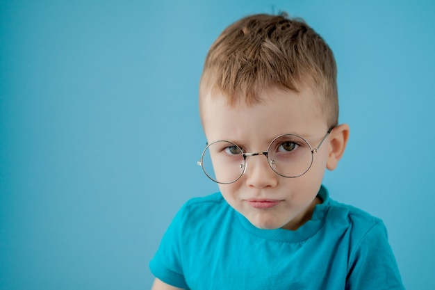 Portret małego uśmiechniętego chłopca w śmieszne okulary. szkoła. przedszkola moda. pracowniany portret na błękitnej ścianie, kopii przestrzeń