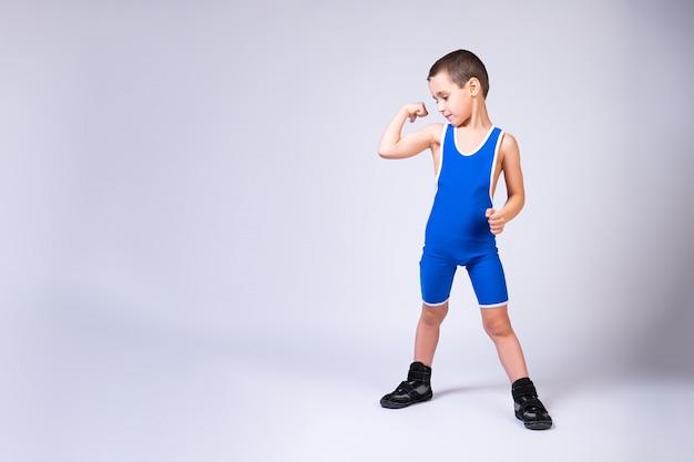 Portret małego wesołego chłopca w niebieskich rajstopach zapaśniczych pokazuje biceps