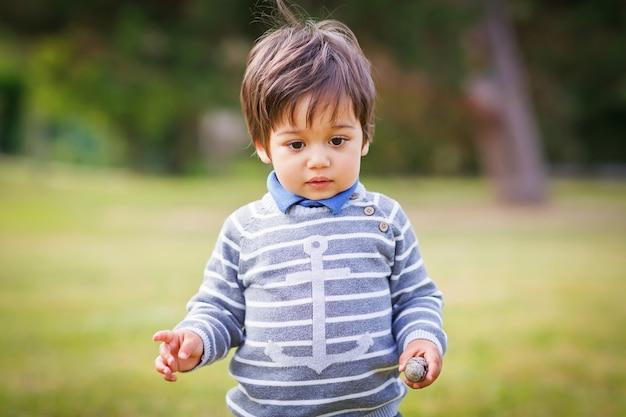Portret małego wschodniego przystojnego chłopca grającego na świeżym powietrzu w parku. arabska zabawa dla dzieci na ulicy.