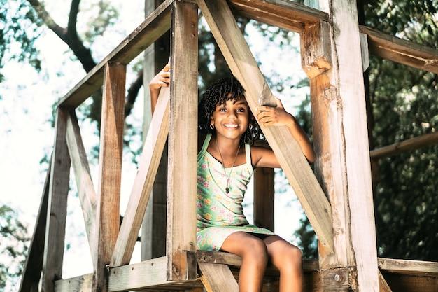 Portret małej afroamerykańskiej dziewczyny siedzącej, patrząc w kamerę. koncepcja szczęścia z dzieciństwa