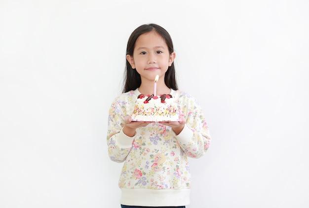 Portret małej azjatyckiej dziewczynki trzymającej tort urodzinowy na białym tle