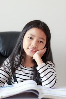 Portret małej azjatyckiej dziewczyny siedzący podbródek i robić pracie domowej dla jaźń uczenie się i edukaci pojęcia