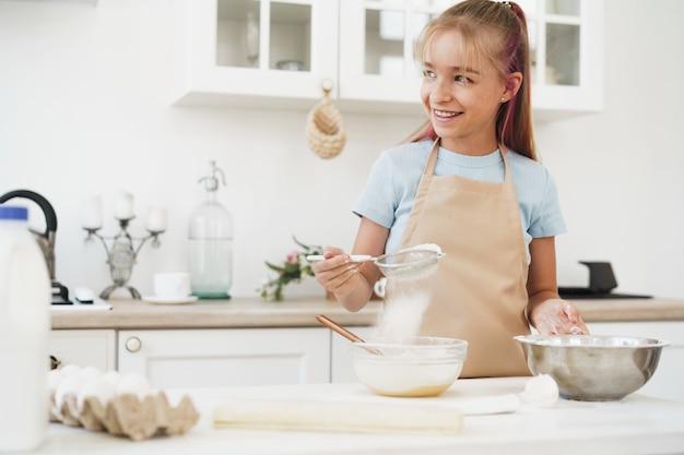 Portret małej blond nastolatki noszącej fartuch w kuchni