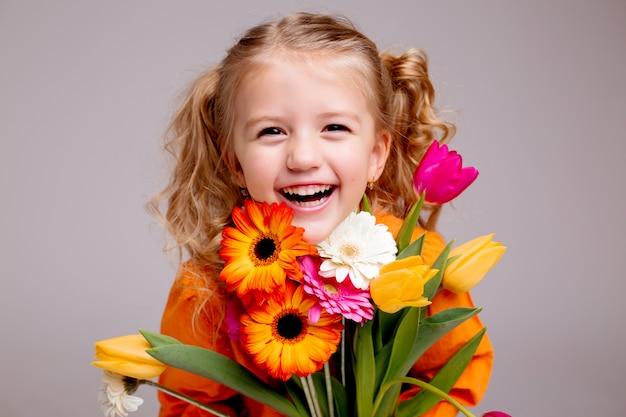 Portret małej blondynki dziewczyny z bukietem wiosennych kwiatów na lekkiej ścianie