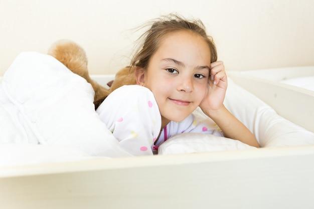 Portret małej brunetki obudziła się rano w łóżku