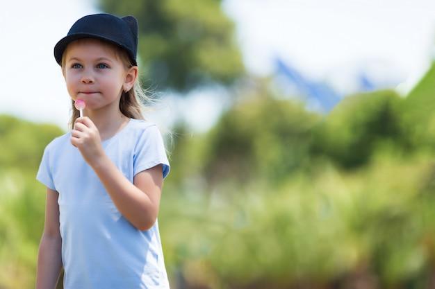 Portret małej charyzmatycznej dziewczyny. mała dziewczynka w nakryciu głowy. dziewczyna z cukierkami