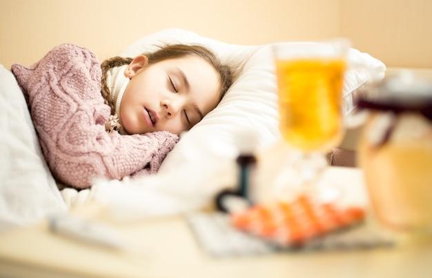 Portret małej chorej dziewczynki w swetrze śpiącej w łóżku