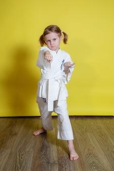 Portret małej dziewczynki ćwiczącej karate na żółtej powierzchni