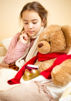 Portret małej dziewczynki leżącej w łóżku z misiem ze słoikiem z miodem