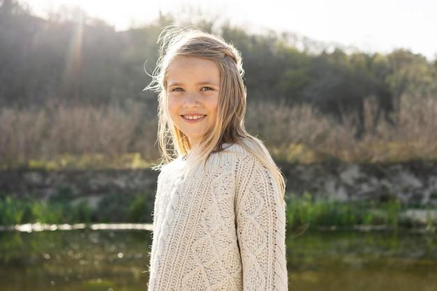 Portret małej dziewczynki na zewnątrz nad jeziorem