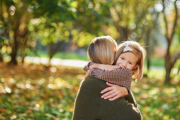 Portret małej dziewczynki obejmującej swoją mamę