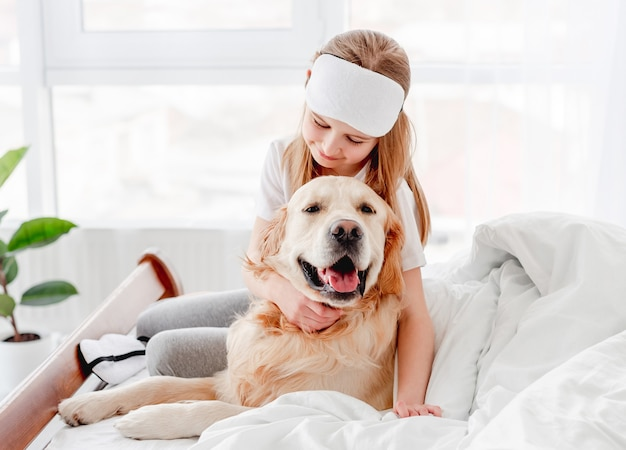 Portret małej dziewczynki przytulanie psa golden retriever w łóżku po przebudzeniu. dziecko przebywające w domu z psem domowych rano i głaszczące go. zwierzę domowe z właścicielem