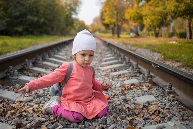 Portret małej dziewczynki siedzącej na torach kolejowych w lesie