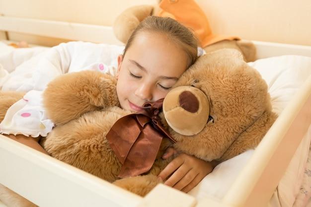 Portret małej dziewczynki śpiącej na dużym misiu w łóżku