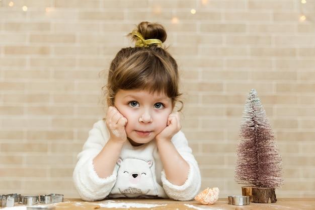 Portret małej dziewczynki z brązowymi kręconymi włosami i dużymi niebieskimi oczami