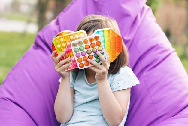 Portret Małej Dziewczynki Z Nowoczesną Zabawką Popit Kolorową I Jasną Zabawką Pop It Prosty Dołek Premium Zdjęcia