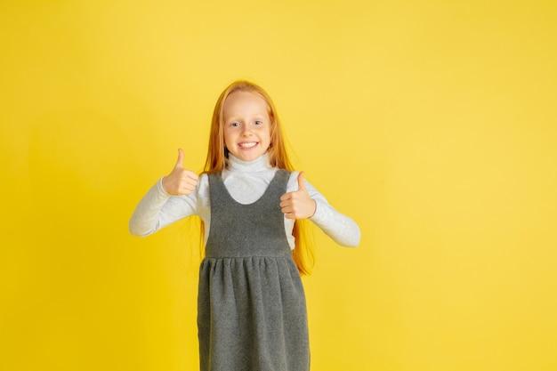 Portret małej kaukaskiej dziewczynki z jasnymi emocjami na żółtym tle studyjnym