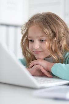 Portret małej słodkiej blondynki korzystającej z komputera