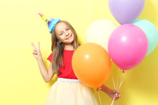 Portret małej słodkiej dziewczynki w świątecznej czapce i z balonami
