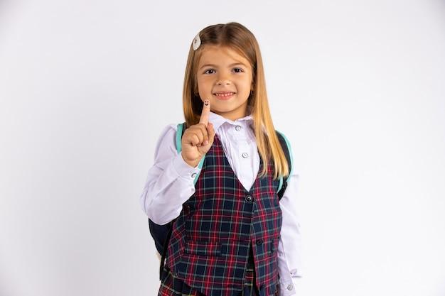 Portret małej uczennicy w mundurku szkolnym ze szczerym uśmiechem. mała dziewczynka wskazuje palcem w górę, na białym tle na białej ścianie z pustą przestrzenią.